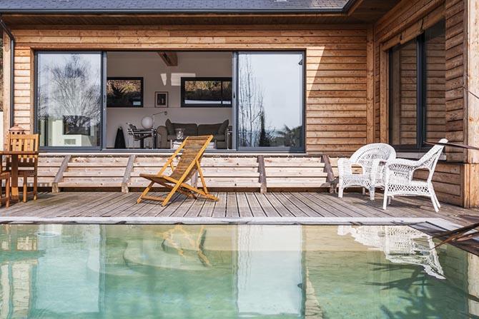 Maison bois. De la piscine et terrasse à l'intérieur