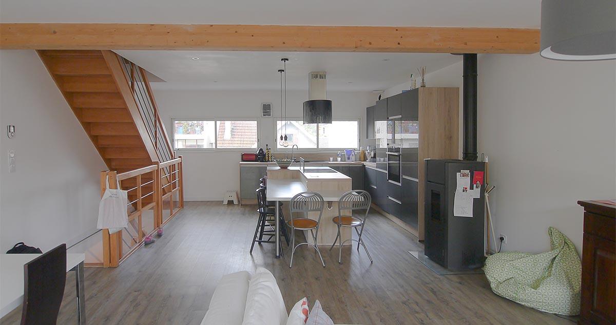 Le poêle à pellets et la cuisine et l'escalier, depuis le salon. Conception réalisation FranceMaisons-idf