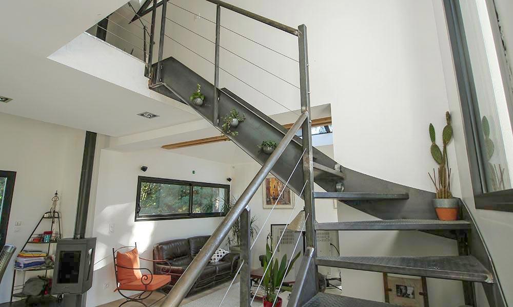 Superbe escalier design métallique éclairé par de grandes baies
