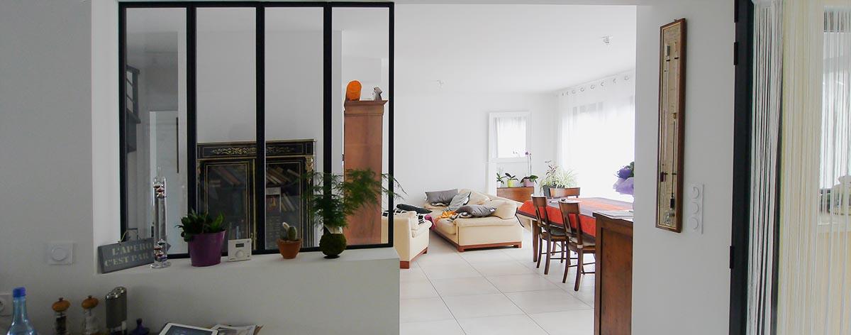 La cuisine mi-ouverte donne sur la salle à manger par la verrière. FranceMaisons.idf